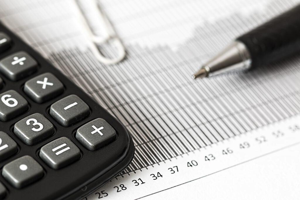 Bild vom Taschenrechner, Büronadel, Kugelschreiber und Tabelle
